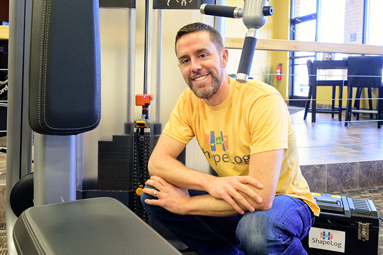 Brian Hayden of ShapeLog with a Universal Strength Tracker on a weight lifting machine